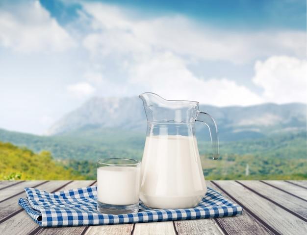 Bicchiere di latte e bottiglia sullo sfondo