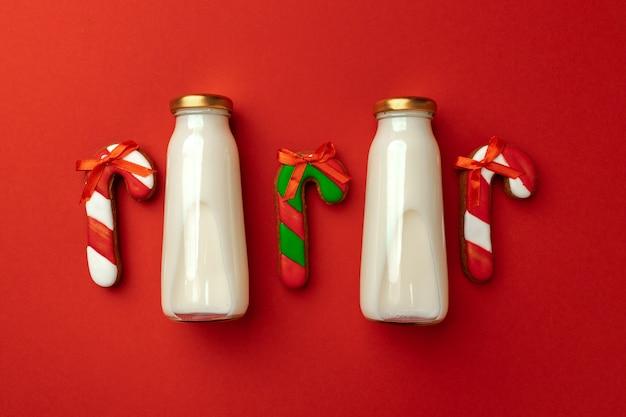 Bottiglia di latte di vetro e biscotti di panpepato di natale su sfondo rosso