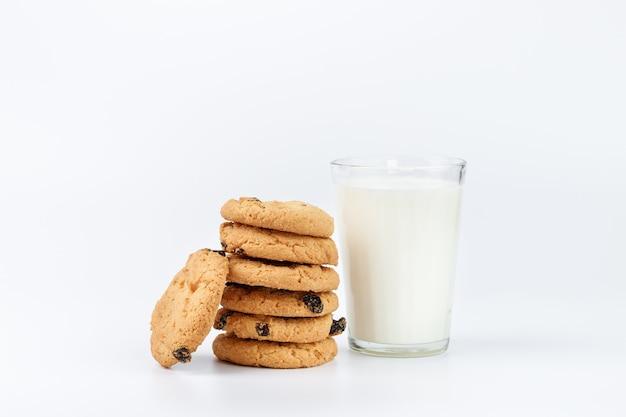 Bicchiere di latte e biscotti con uvetta isolata