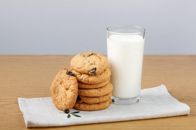 Bicchiere di latte e biscotti con uvetta sul tavolo