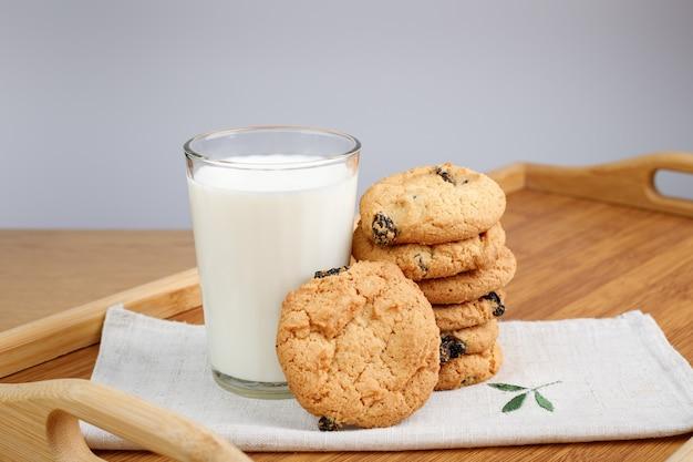 Bicchiere di latte e biscotti con uvetta su un vassoio di legno