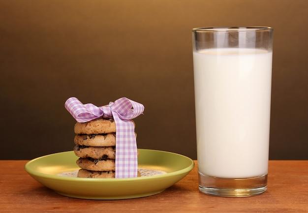 Bicchiere di latte e biscotti sulla tavola di legno su fondo marrone