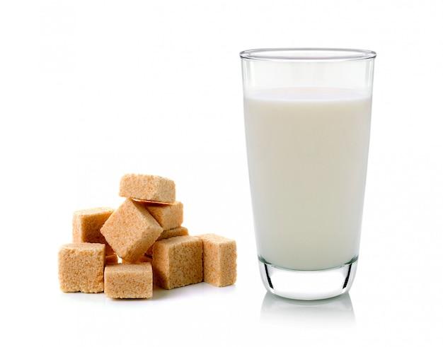 Bicchiere di latte e cubetti di zucchero di canna isolati su spazio bianco