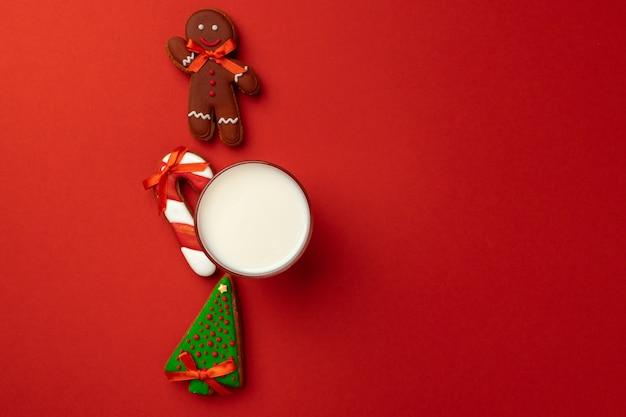Bicchiere di latte e biscotti di panpepato su sfondo rosso