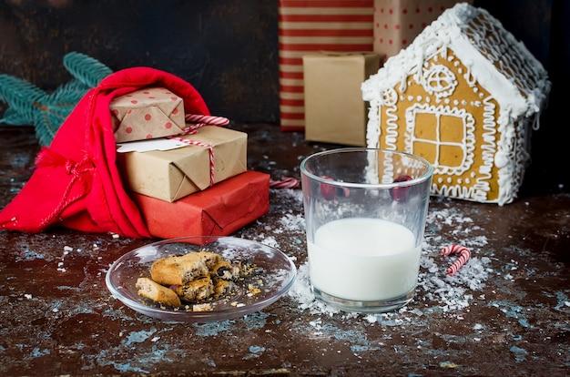 Bicchiere di latte e biscotti fatti in casa con cioccolato a babbo natale sul tavolo, decorazioni natalizie,