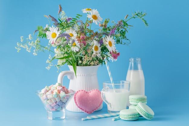 Bicchiere di latte con dolci e amaretti di paglia a strisce