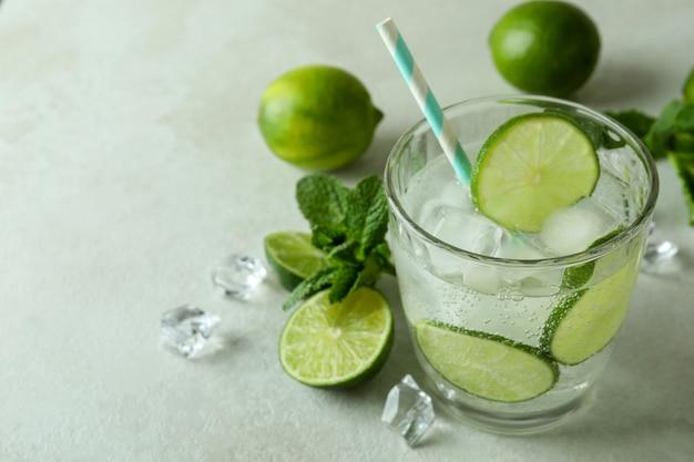 Bicchiere di mojito cocktail e ingredienti su sfondo bianco con texture