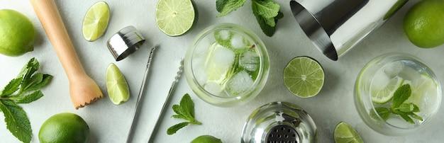 Bicchiere di mojito cocktail e ingredienti sulla tabella testurizzata bianca
