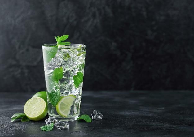 Bicchiere di cocktail mojito con cubetti di ghiaccio menta e lime su sfondo nero