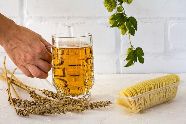 Boccale di birra di vetro in mano di una donna con patatine fritte, spighe d'orzo e un ramo di luppolo sullo sfondo bianco.