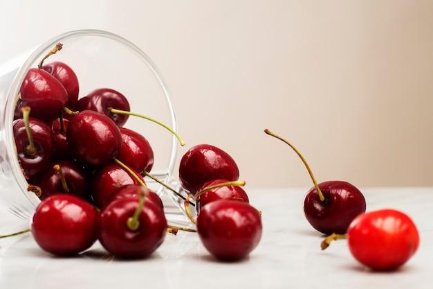 Tazza in vetro adagiata sul tavolo con ciliegie