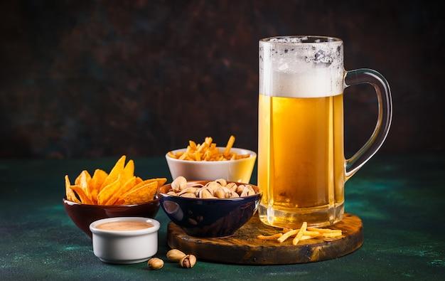 Boccale di vetro con birra con schiuma e gocce d'acqua e snack su verde scuro
