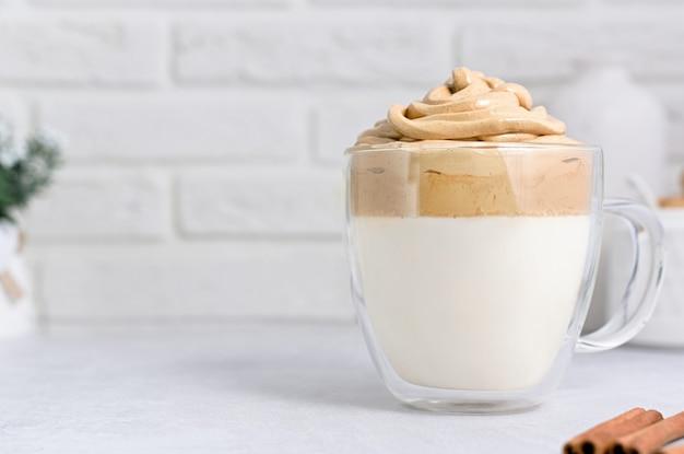 Una tazza di vetro con caffè dalgona su sfondo chiaro con spazio copia Foto Premium
