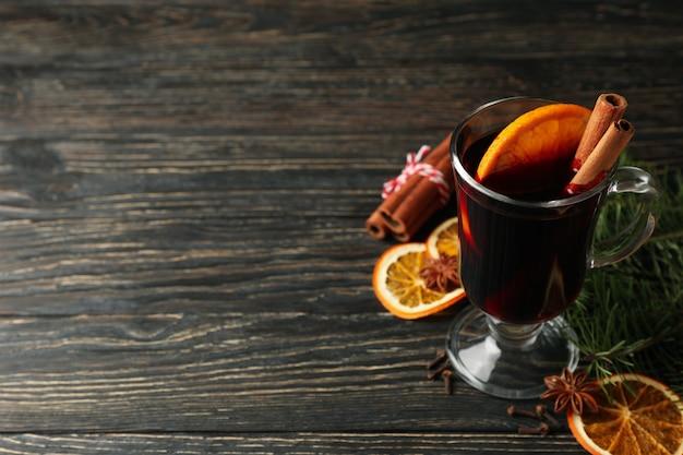 Bicchiere di vin brulè e ingredienti sulla tavola di legno