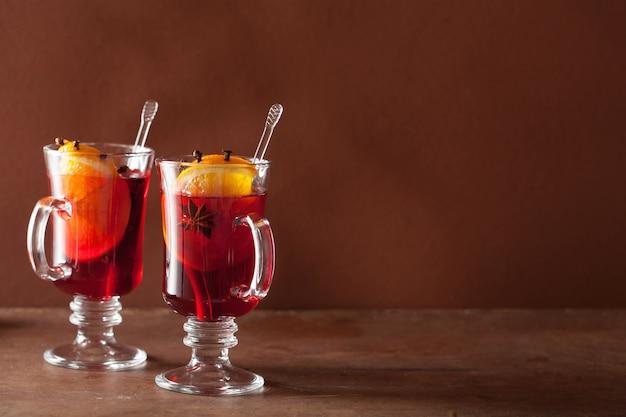 Bicchiere di vin brulè con arancia e spezie, stagione invernale