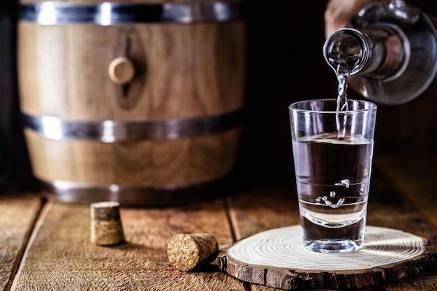 Bicchiere traboccante di alcol, che scorre lungo il tavolo, gocce che volano, schizzi