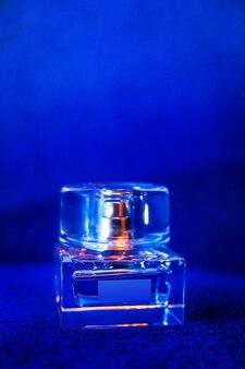 Bottiglia di profumo di vetro su sfondo blu.