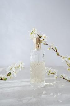 Bottiglia di profumo di vetro con rami di ciliegio in fiore su grigio