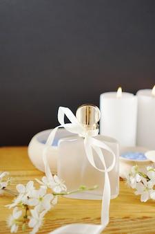Bottiglia di profumo di vetro con un fiocco di nastro e fiori di sakura sul tavolo di legno