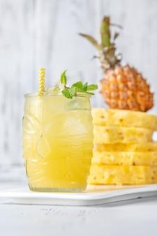 Bicchiere di ananas tiki stile cocktail sul tavolo bianco