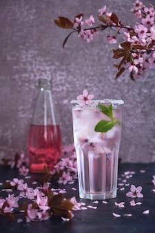 Bicchiere di champagne rosa rosa, sidro o limonata con ghiaccio e menta e fiori di ciliegio