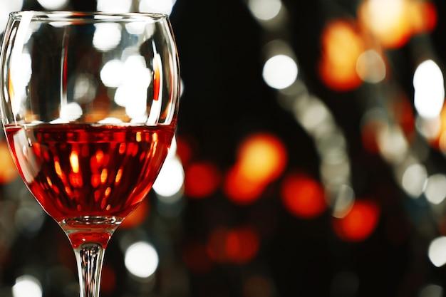 Un bicchiere di vino rosa su una superficie illuminata sfocata