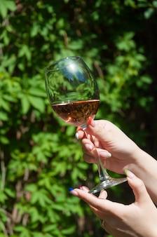 Un bicchiere di vino rosa nelle mani di una ragazza su uno sfondo di foglie verdi