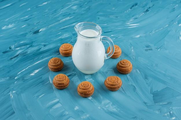 Una brocca di vetro di latte fresco con biscotti dolci rotondi su una superficie blu