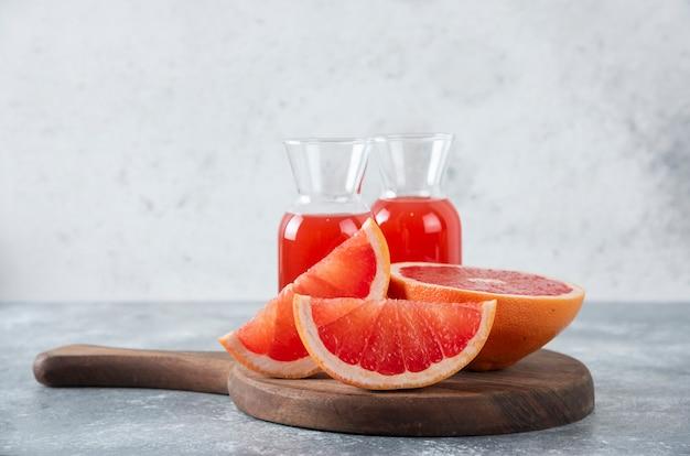 Brocche di vetro di succo di pompelmo fresco con fette di frutta poste su una tavola rotonda di legno.