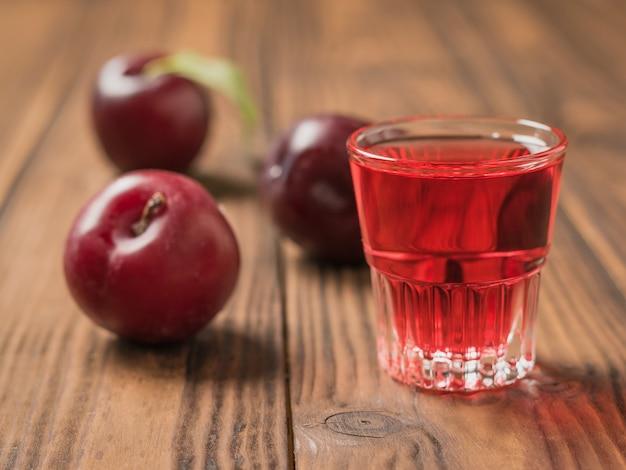Un bicchiere di liquore alla prugna e bacche di prugne sul tavolo del villaggio. bevanda alcolica fatta in casa a base di prugne frutti di bosco.