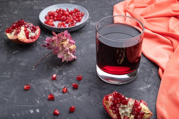 Bicchiere di succo di melograno su uno sfondo di cemento nero con tessuto rosso.