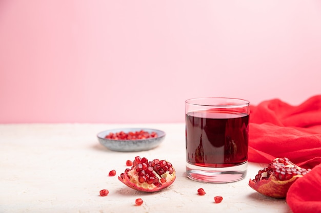 Bicchiere di succo di melograno su uno sfondo bianco e rosa con tessuto rosso.