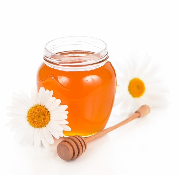 Vaso di vetro con miele floreale isolato su priorità bassa bianca.