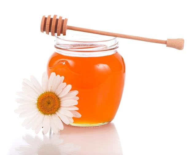 Vaso di vetro con miele floreale isolato su superficie bianca
