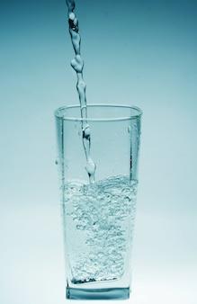 Bicchiere d'acqua versando con la riflessione