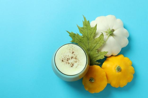 Bicchiere di latte di zucca e ingredienti su sfondo blu