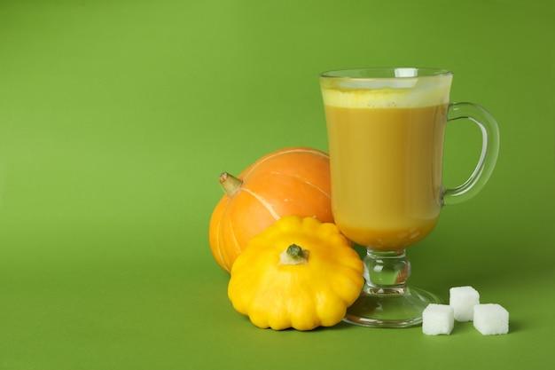 Bicchiere di latte di zucca e ingredienti su sfondo verde