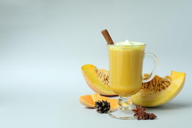 Bicchiere di latte di zucca e ingredienti su sfondo grigio chiaro