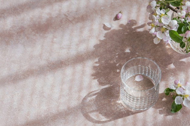 Bicchiere di acqua pura sul tavolo con ramo di melo in fiore in un bicchiere. umore di sole mattutino