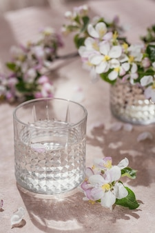 Bicchiere di acqua pura sul tavolo con ramo di melo in fiore in un bicchiere