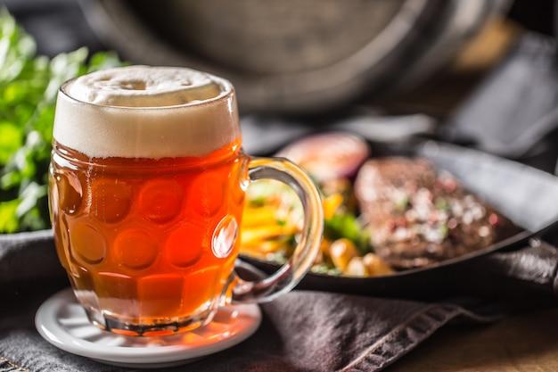 Bicchiere di birra rossa in pub o ristorante sul tavolo con cibo delizioso.