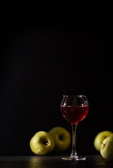 Bicchiere di vino rosso frutto isolato su fondo nero. fresco raccolto di mele, natura morta in chiave di basso profilo. copia spazio.