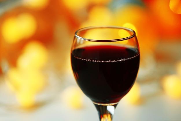 Un bicchiere di vino rosso su sfondo sfocato