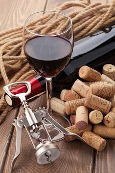Bicchiere di vino rosso, bottiglia, mucchio di tappi di sughero e cavatappi su tavola in legno rustico