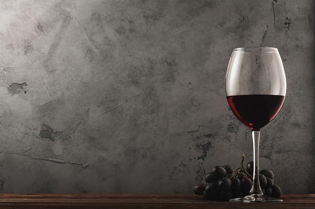 Un bicchiere di vino rosso e un grappolo d'uva su un vecchio tavolo di legno. sfondo scuro.