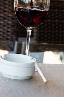 Bicchiere di vino rosso e sigaretta in un posacenere bianco sul tavolo in un caffè di strada, estate sulla veranda di un ristorante, cattive abitudini, alcolismo e fumo di tabacco