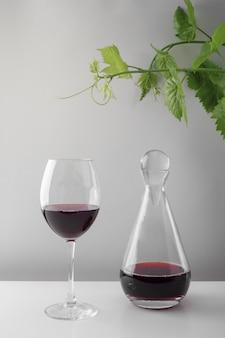 Un bicchiere di vino rosso e un decanter su un tavolo bianco. sfondo chiaro.