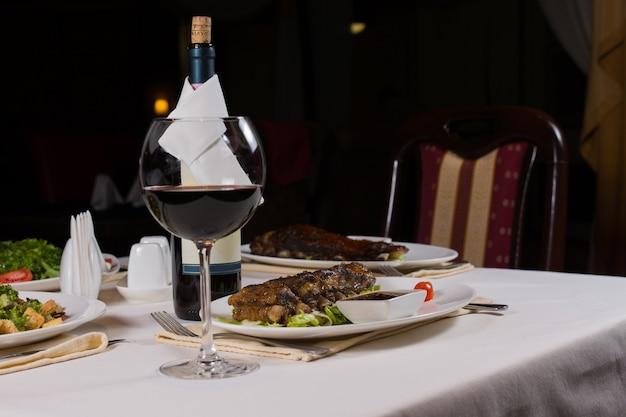 Bicchiere di vino rosso sul tavolo fantasia con cena servita nel ristorante