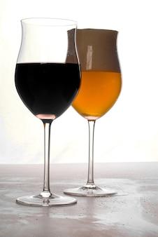Bicchiere di vino rosso e un bicchiere di birra chiara su sfondo bianco.