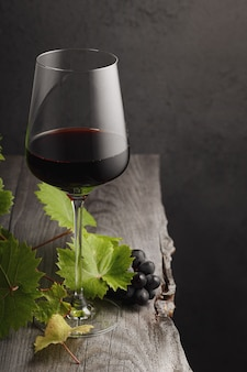 Un bicchiere di vino rosso, uva e foglie di vite su un vecchio tavolo di legno. sfondo scuro.
